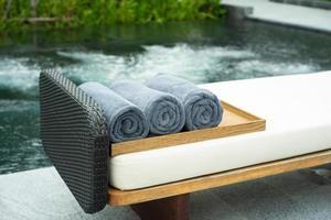 gros plan de rouleaux de serviettes sur le plateau en bois sur un lit de plage avec un bain à remous bulle floue en arrière-plan. industrie du spa photo