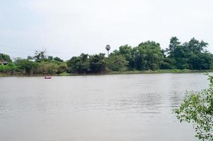 photo de paysage d'un pêcheur ramant un bateau pour pêcher au milieu d'une rivière.