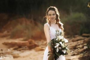 mariée avec un bouquet de mariage au bord de la mer photo