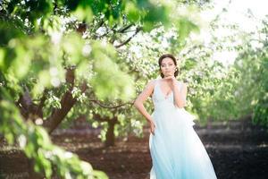 fille brune dans une robe turquoise dans le jardin de printemps photo