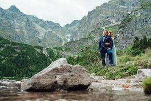 jeune couple en promenade près du lac entouré par les montagnes photo