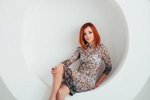 Fille modèle aux cheveux rouges sur fond de cercle blanc photo
