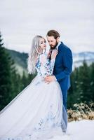 Marié dans un costume bleu et mariée en blanc dans les montagnes des Carpates photo