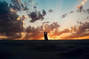 jeune couple un mec en culotte noire et une fille en robe rose marchent le long du sable blanc photo