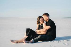 jeune couple, un mec et une fille avec des émotions joyeuses dans des vêtements noirs marchent à travers le désert blanc photo