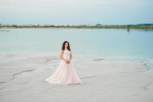fille dans une robe rose marchent le long du sable blanc photo
