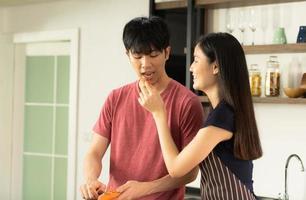 un jeune couple asiatique mange ensemble et sourit joyeusement tout en cuisinant leur salade dans la cuisine. photo