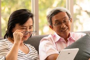 Senior homme asiatique et femme se détendre en vacances dans le fond de salon naturel avec la technologie moderne photo