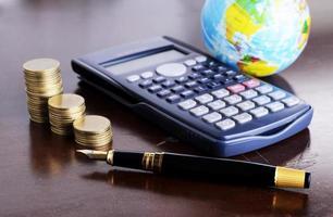 Pièces d'argent calculatrice avec stylo-plume et terre pour le concept de prêt d'argent photo