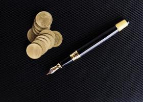 Stylo-plume et pile de pièces sur fond de cuir pour concept d'entreprise photo