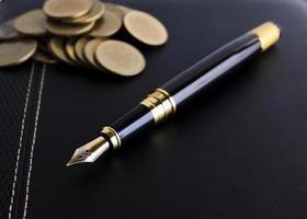 Stylo-plume et pile de pièces sur livre en cuir pour concept de financement d'entreprise photo