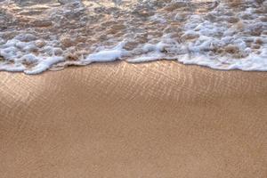 Vague de mer tropicale brillante avec bulle sur la plage brune au coucher du soleil photo