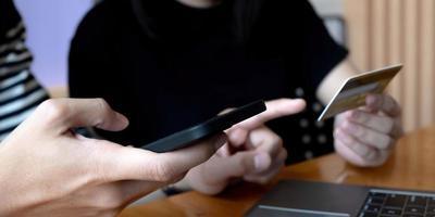 Mise au point sélective de l'homme positif tenant le smartphone tout en utilisant une carte de crédit près de femme photo