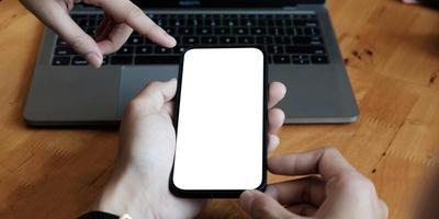Deux mains mâles à l'aide de smartphone la nuit sur la rue commerçante de la ville, la recherche ou le concept de réseaux sociaux photo