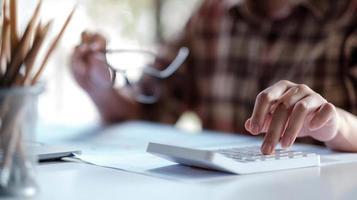 Gros plan de femme ou comptable main tenant un stylo travaillant sur la calculatrice pour calculer les données commerciales, le document de comptabilité et l'ordinateur portable au bureau photo