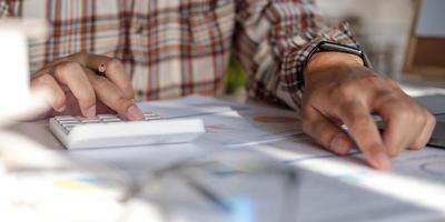 homme d'affaires mains tenant un stylo travaillant sur la calculatrice et la paperasse financière photo