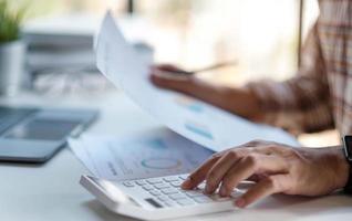homme d'affaires ou comptable main tenant un stylo travaillant sur la calculatrice pour calculer les données commerciales, document de comptabilité avec ordinateur portable sur les bureaux. photo
