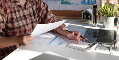 photo de mains tenant un stylo sous le document et en appuyant sur les boutons de la calculatrice