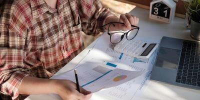 Gros plan de femme d'affaires ou comptable main tenant un stylo travaillant sur la calculatrice pour calculer les données commerciales, document de comptabilité et ordinateur portable au bureau, concept d'entreprise photo