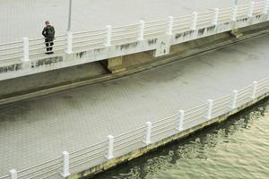 un homme non identifié se tient sur la passerelle en béton le long de la rive de la rivière avec le reflet de la lumière du coucher du soleil. photo