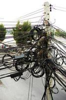 Câbles en désordre dans un poteau de béton électrique à côté de la route dans la ville photo