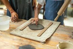 Gros plan des mains d'une fille à l'aide d'un rouleau à pâtisserie sur l'argile pendant la classe de l'atelier de moulage photo