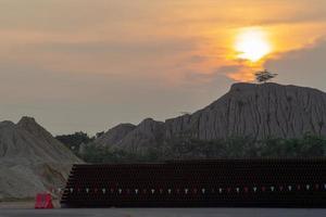 silhouette d'un arbre sur une montagne avec un coucher de soleil et un ciel crépusculaire en arrière-plan photo