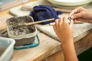 Mouvement des mains floues d'une fille de moulage d'argile avec de la boue humide dans un bac en plastique photo