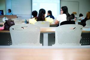 Mise au point sélective sur la rangée de chaises vides avec groupe d'étudiants flou en arrière-plan photo