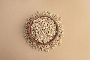 Vue de dessus bol avec grains de café non torréfiés photo
