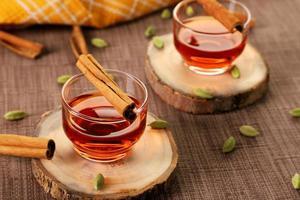 thé à la cannelle sur des tranches de bois photo