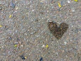 Texture abstraite et fond de route de ciment sale à partir d'huile lubrifiante du véhicule en forme de coeur avec la chute de petites feuilles autour photo