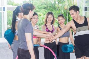 jeune groupe joint les mains avant de faire de l'exercice dans la salle de gym. concept d'une nouvelle génération soucieuse de la santé photo