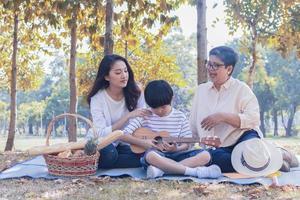 la famille asiatique aime s'asseoir dans le parc pendant les vacances d'automne. photo
