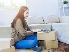 belle femme asiatique assise à la maison et travaillant en ligne. entreprise d'expédition en ligne. photo