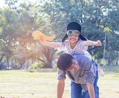 père et fils jouant des avions en papier dans le parc. le fils est sur le dos de son père. photo