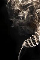 fumée abstraite d'incane sur fond noir ressemble au visage. photo