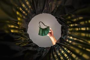 jeter un masque facial à la poubelle. avec une vue de ver de l'intérieur de la poubelle. photo