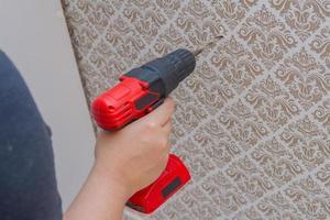 Femme collant un mur avec une perceuse rouge dans sa main photo