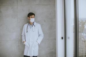 médecin portant un masque regardant par la fenêtre photo