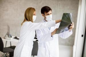 médecins masqués examinant une radiographie photo