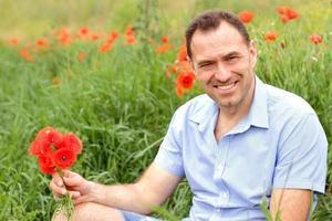 homme souriant dans un champ de pavot photo