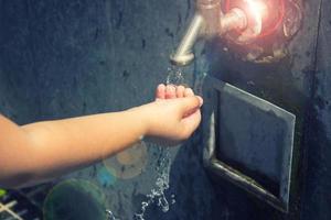 petite fille se lave la main dans la fontaine publique photo