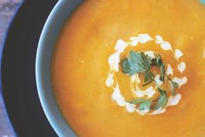 Close up de soupe à la citrouille dans un bol bleu photo