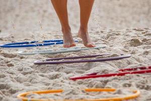 pieds faisant des exercices sur une échelle d'exercice fonctionnelle sur le sable de la plage. photo