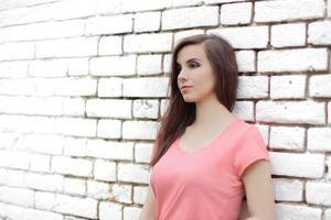 femme appuyée sur un mur de briques blanches photo