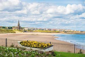 Bateau d'ornement contenant des fleurs, avec le littoral de Tynemouth en arrière-plan photo
