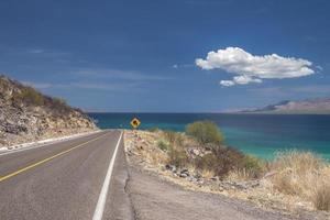 punta armenta en bahia concepcion baja california sur mexico avec ciel bleu et la mer de cortes sur l'arrière-plan et l'autoroute de loreto à santa rosalia sur les montagnes à mulege photo