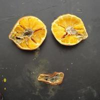 Un visage laid formé avec des morceaux d'orange pourris sur fond noir sale photo