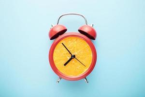 une horloge orange sur fond bleu photo